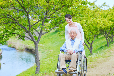 caregiver and senior man strolling