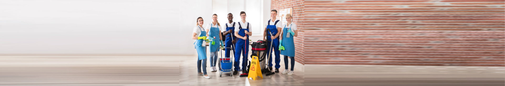 Portrait Of Happy Diverse Janitors In The Office With Cleaning Equipment